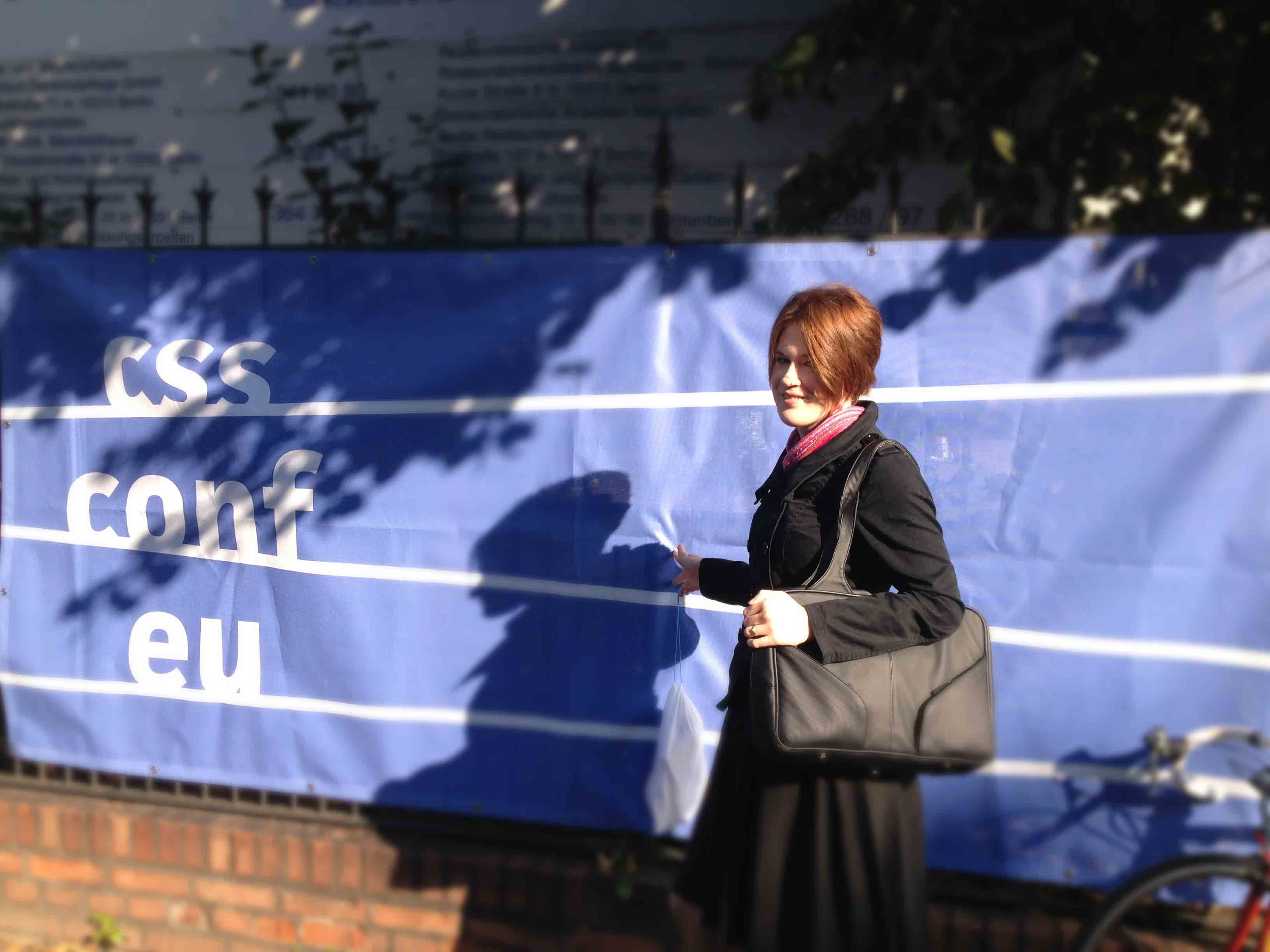 Me in front of the CSS Conf EU banner on a sunny Berlin day, dappled in tree shade.