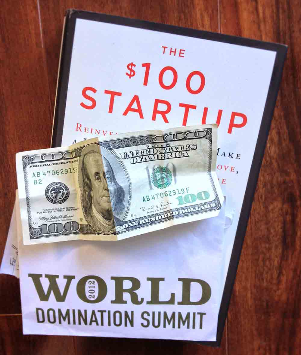 'The $100 Startup' book and a hundred dollar bill