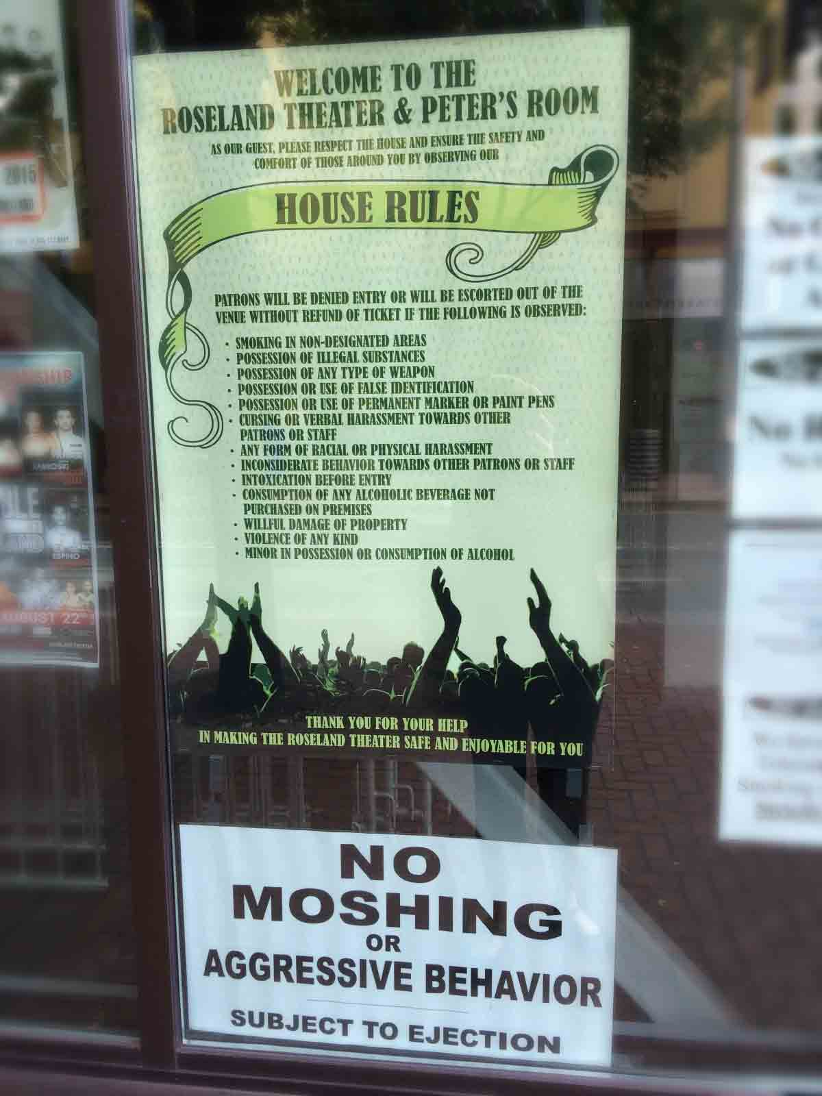 A bunch of signs in a window saying no moshing or harmful behavior, kids.