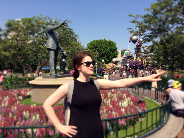 At Disneyland: Rachel Nabors stands and points in front of a statue of Walt Disney, also pointing, with Mickey Mouse at his side.